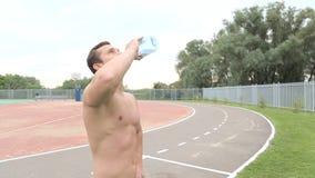 Sunt dricksvatten för ung man från flaskan utomhus stock video