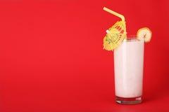Sunt exponeringsglas av smoothiesbanananstrykning på rött Royaltyfri Fotografi