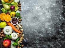 Sunt färgrika sunda örter för äta -, kryddor, frukter och grönsaker på svart, stenar tabellen royaltyfri foto