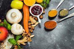 Sunt färgrika sunda örter för äta -, kryddor, frukter och grönsaker på svart, stenar tabellen fotografering för bildbyråer