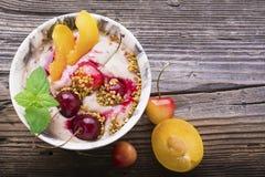 Sunt frukostmellanmål Marmordelbunke mycket av den körsbärsröda smoothien med den naturliga yoghurten, mogna bär, frukter, bi Arkivbild