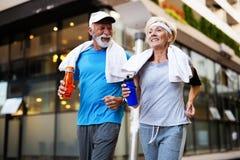 Sunt högt, par som joggar i staden på ottan med soluppgång arkivfoto