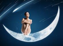 Sunt kvinnasammanträde på den skinande månen arkivfoto