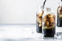 Sunt mat- och drinkbegrepp: kall svart detoxmineralvatten med krossad is i glasflaskor, med aktiverat kol som är grått royaltyfri bild