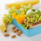 Sunt mellanmål i blå plast- lunchask på den vita trätabellen arkivbild
