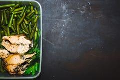 Sunt mellanmål, mat i en behållare Bakad röd fisk, rosa lax, lax och haricot vert på svart bakgrundsslut upp Top beskådar arkivfoto
