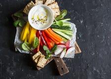 Sunt mellanmål - rå grönsaker och yoghurtsås på en träskärbräda, på en mörk bakgrund, bästa sikt sund vegetarian för mat fotografering för bildbyråer