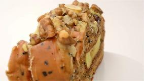 Sunt och smaskigt bröd med den valnötrussinet och melon kärnar ur att rotera på vit arkivfilmer