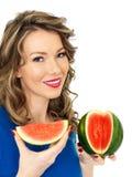 Sunt skivad vattenmelon för ung kvinna innehav Arkivbild