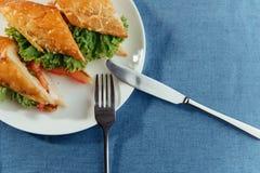 Sunt smörgåssnitt in i stycken som visar smaklig ingredienssalam Arkivfoto