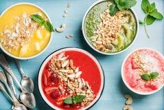 Sunt sommarfrukostbegrepp Den färgrika fruktsmoothien bowlar på turkosblåttbakgrund fotografering för bildbyråer