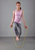 Sunt ungt muskulöst överhopprep för tonårs- flicka i studio Barn som övar med banhoppning på grå bakgrund Arkivbild