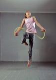 Sunt ungt muskulöst överhopprep för tonårs- flicka i studio Barn som övar med banhoppning på grå bakgrund Royaltyfri Bild