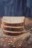 Sunt wholegrain bröd på säckvävservetten som lokaliseras på träbaksida Royaltyfri Fotografi