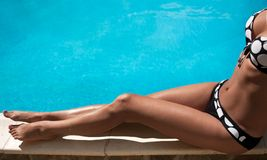 Suntan. Young woman sitting on the ledge of the pool Stock Photography