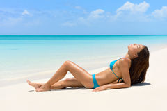 Suntan bikini woman relaxing on beach vacation. Sunbathing/sun tanning on perfect white sand turquoise beach for summer holidays. Asian model with body and blue stock image