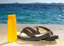 Suntan cream or oil and sandals on beach Stock Photography