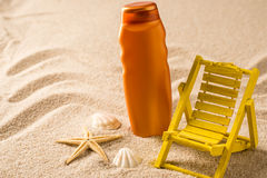 Suntan lotion container and seashells on sand Royalty Free Stock Photo