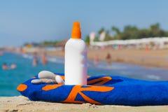 Suntan lotion, pebbles, towel on pier. Under the hot summer sun Royalty Free Stock Photos