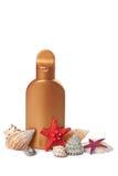 Suntan lotion and sea shells isolated Royalty Free Stock Photography