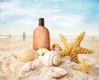 Suntan lotion and seashells on the beach Royalty Free Stock Photos
