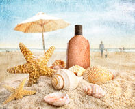 Suntan lotion and seashells on the beach royalty free stock images