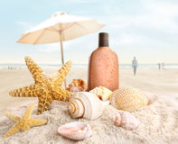 Suntan lotion and seashells on the beach Stock Image