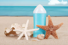Suntan lotion with shells on the beach Stock Images