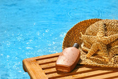 Suntan lotion and straw hat Stock Photo