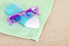 Suntan lotion sun glasses and beach towel Stock Image