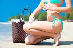Suntan lotion and sunscreen. Woman applying Stock Photos