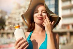 Suntan lotion. Woman applying sunscreen solar cream on face. Beautiful happy cute girl puts suntan cream from plastic royalty free stock photography