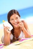 Suntan lotion woman applying sunscreen solar cream. Laughing having fun. Beautiful happy cute woman asian applying suntan cream from a plastic container to her Stock Image