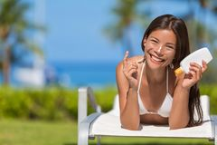 Suntan lotion woman applying sunscreen. Solar cream. Beautiful happy cute woman asian applying suntan cream from a plastic container to her nose with ocean in royalty free stock images