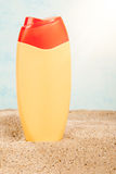Suntan plastic bottle on the sand Stock Photos