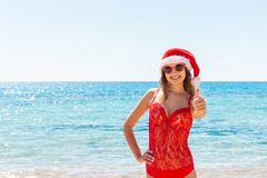Suntan young woman slim in santas hat and red bathing suit relaxing tropical sand beach. christmas winter vacation holiday concept stock photos