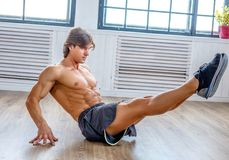 Suntanned athletic male doing stomach workouts. Suntanned athletic male doing stomach workouts on the floor in natural soft light Stock Photos