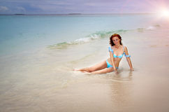 Suntanned beautiful young woman has a rest in surf waves. The suntanned beautiful young woman has a rest in surf waves Stock Image