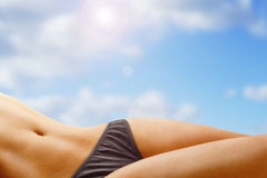 Suntanned body of a young woman. Perfect female body on the beach Stock Image