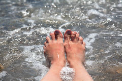 Suntanned female feet. In sea water Royalty Free Stock Photography
