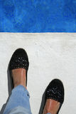 Suntanned female feet at the edge of the pool Royalty Free Stock Photo