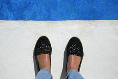 Suntanned female feet at the edge of the pool Royalty Free Stock Photos
