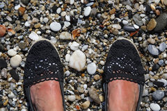 Suntanned female feet on a rocky beach. Summer vacation selfie suntanned female feet on a rocky beach Royalty Free Stock Photo