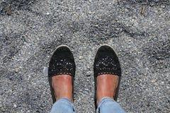 Suntanned female feet on a rocky beach Royalty Free Stock Photos