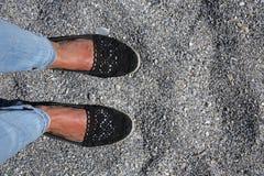 Suntanned female feet on a rocky beach Stock Photos