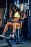 Suntanned fitness female exercising in a gym. Suntanned fitness female exercising on multi action machine in a gym club Stock Image