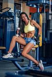 Suntanned fitness female exercising in a gym. Suntanned fitness female exercising on multi action machine in a gym club Royalty Free Stock Photography