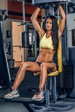 Suntanned fitness female exercising in a gym. Suntanned fitness female exercising on multi action machine in a gym club Royalty Free Stock Photos