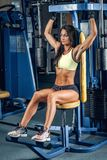Suntanned fitness female exercising in a gym. Suntanned fitness female exercising on multi action machine in a gym club Stock Photos