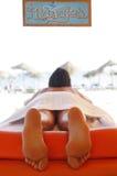 Suntanned Frau, die auf Massagetabelle liegt Stockfotografie